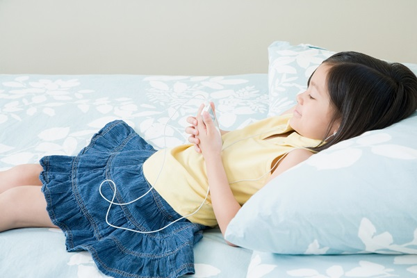 Girl on bed listening to MP3 player