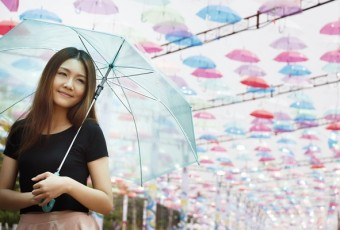 Smiling Asian girl with umbrellas as background.