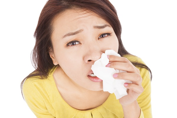 Sneezing and blowing nose,  young woman struggles with cold