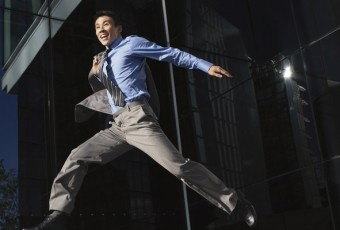 Businessman, jacket over shoulder, Jumping outside building