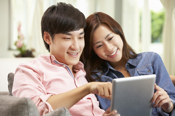 Young Chinese Couple Using Digital Tablet
