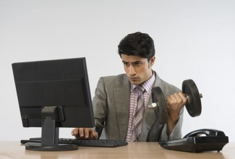 Businessman exercising with dumbbells and working on a computer