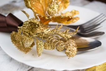 Christmas table setting in gold and brown tone on wood