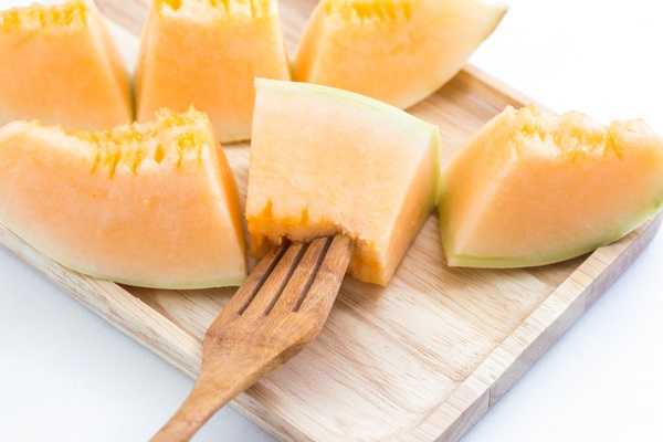Juicy cantaloupe melon with fork on a wooden plate