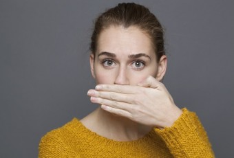 portrait of surprised young woman covering her mouth for silence