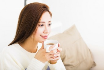 young woman drinking coffee and sitting on sofa