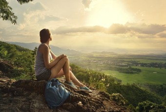 Girl sits on edge cliff and looking at sun valley