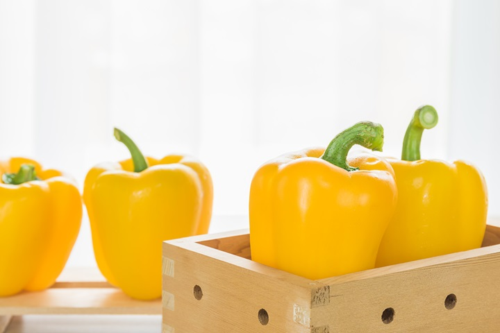 Fresh yellow bell peppers in box