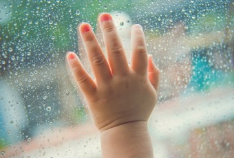 Rain drops on the car window and children hand .