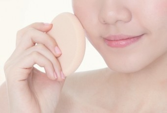 Woman applying foundation on face with cosmetic sponge