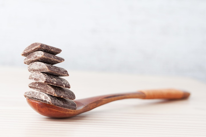 Dark cooking chocolate chunks on wooden spoon with copy space