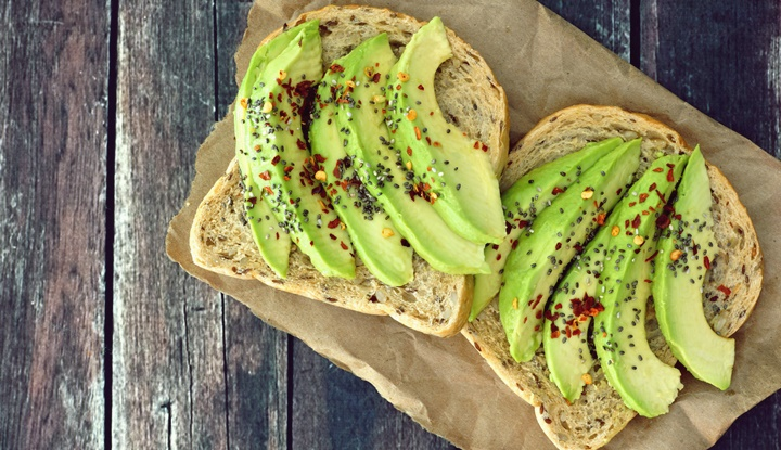 Open avocado sandwiches on paper against rustic wood