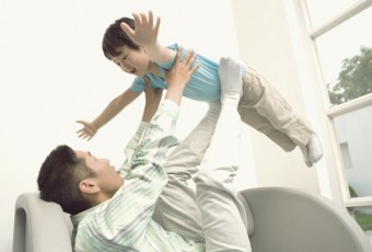 Father playing with his child on a sofa in the living room