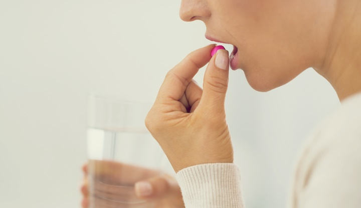 closeup on young woman eating pill