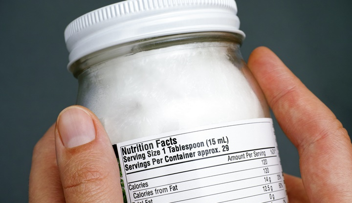 Reading nutrition facts on organic coconut oil jar