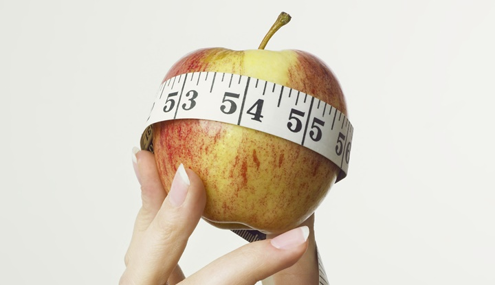 Apple and tape measure in hand