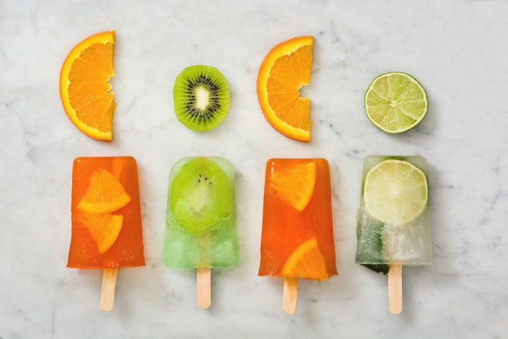 Orange popsicle kiwi popsicles and lime popsicle on marble table