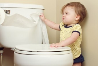 Baby pulling toilet paper off the roll