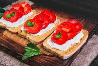 Three sweet fruit sandwich with strawberry, mint on a cutting board on sackcloth with blue lace on a black wooden background surface