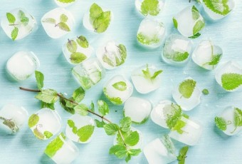 Ice cubes with frozen mint leaves inside on blue Turquoise background, top view, horizontal composition