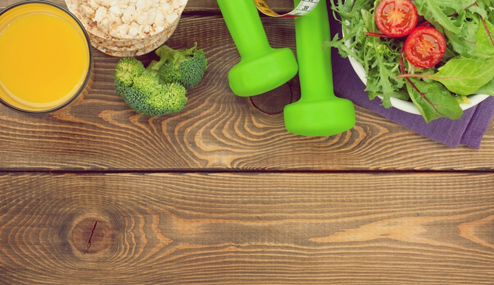 Dumbells, tape measure and healthy food over wooden background