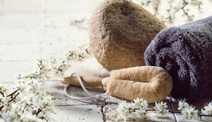 loofah and towel over fresh flowers for exfoliation spa treatment