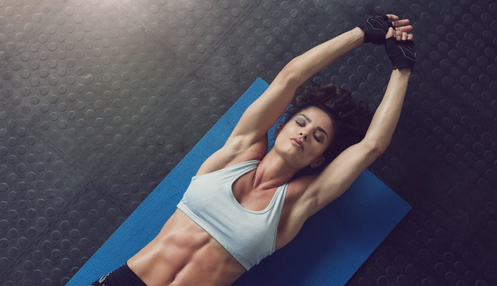 Woman lying on mat doing stretching exercise