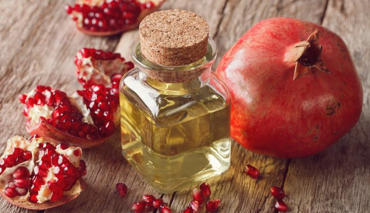 Pomegranate seed oil in a glass bottle on table. Horizontal
