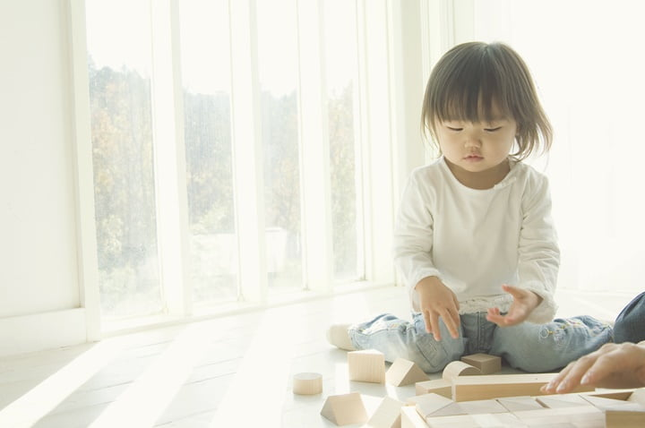 Japanese daughter playing with blocks by window