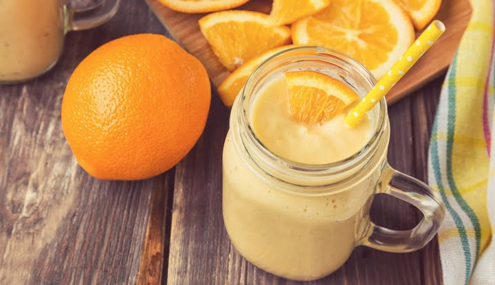 Orange fruit smoothie in the glass jar