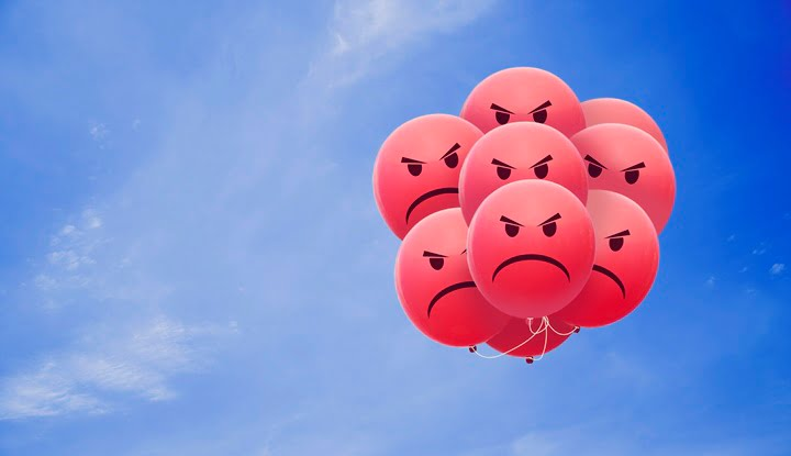 Bright angry balloons flying in the blue sky