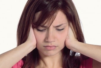 Young woman holding face with hands due to painful Tinnitus