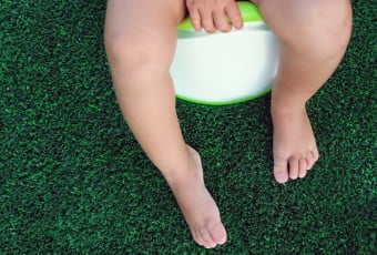 Children's legs hanging down from a chamber-pot. Green background