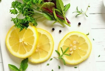 fresh garden herbs and lemon on a white surface