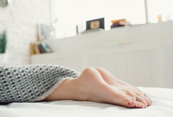 Woman feet on bed under blanket