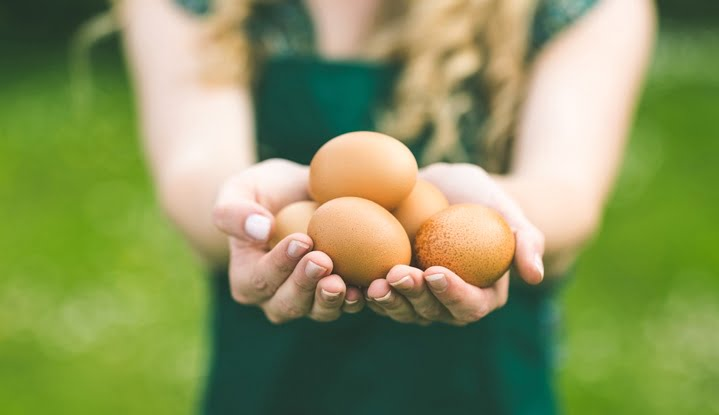 Young woman showing eggs
