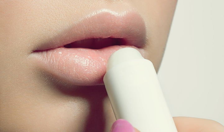 Female lips with a protective balm