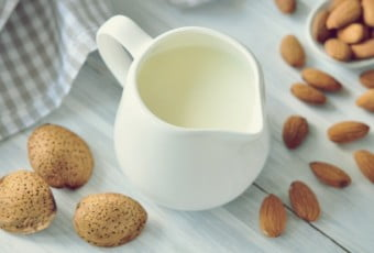 Small jug of almond milk and raw almonds on a white table