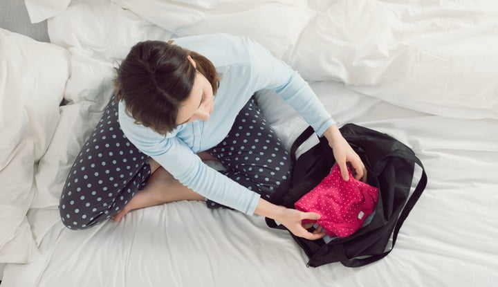 Pregnant Woman Packing Baby Clothes Into Bag