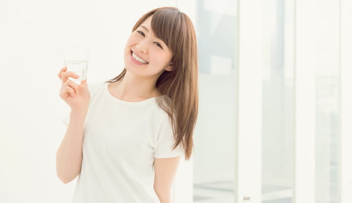 Japanese woman holding a glass of water