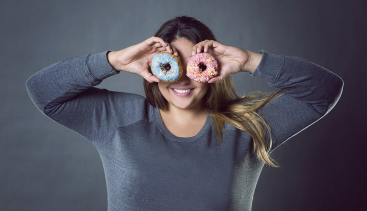 Happy beautiful young caucasian plus size model posing with donuts