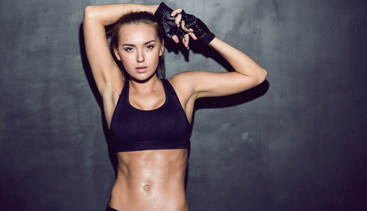 Young woman wearing black sports bra and gloves