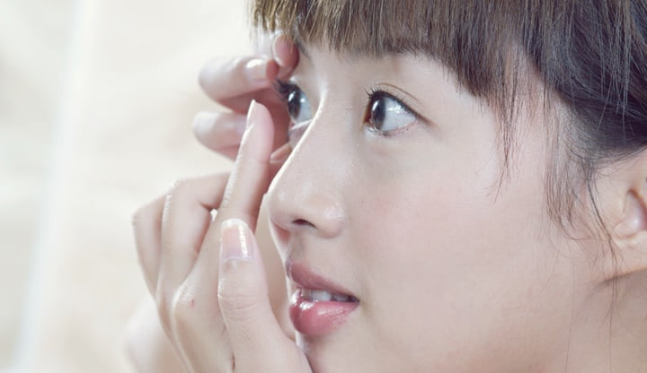 A young woman wearing contact lenses