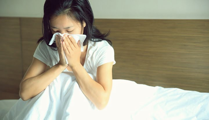 Woman sitting up in bed and sneezing