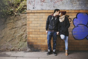 Affectionate teenage couple kissing on street