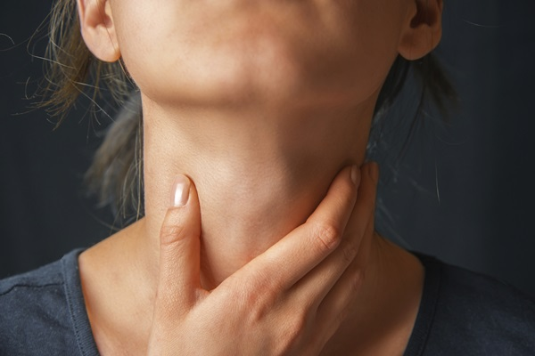 Woman holds her throat, sore throat