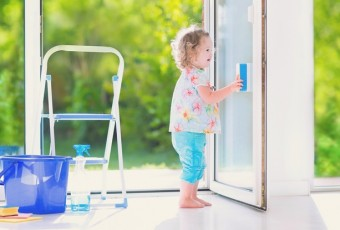 Funny toddler girl washing a window