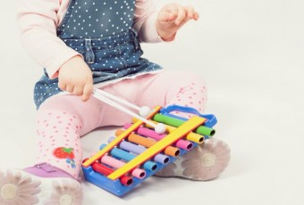 Funny baby girl playing by xylophone