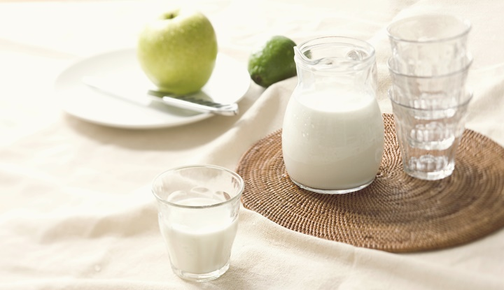 Granny Smith apple, a jug and a glass of milk