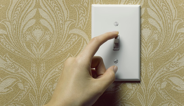 Woman turning off light switch on beige wallpapered wall, close-up